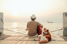 A Man Wear Straw Hat And Playing Guitar Music Song Near The Sea Sunset With A Dog Pet.