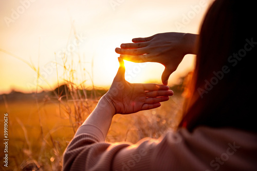 Fototapeta Future planning concept, Close up of woman hands making frame gesture with sunset, Female capturing the sunrise. obraz