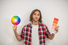 Young Man Holding Color Palette And Looking Uncertain