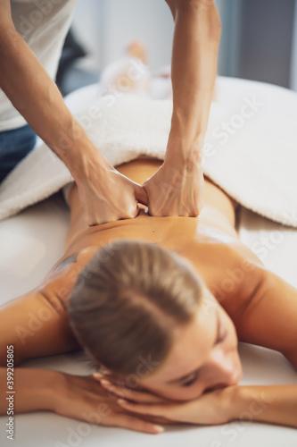 Obraz Professional masseur doing therapeutic massage. Woman enjoying massage in her home. Young woman getting relaxing body massage. - fototapety do salonu