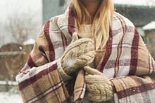 Woman In Mittens And Plaid In Snowy Weather