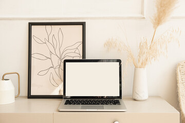 Laptop computer with blank screen pastel beige on table with boho decorations. Pampas grass bouquet, photo frame. Minimal boho styled interior design template with mockup copy space.