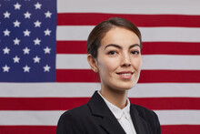Portrait Of Smiling Female Politician Looking At Camera While Standing Against USA Flag Background, Copy Space