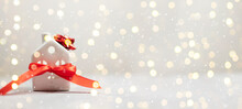 Small Toy Model House And Red Ribbon Bow On White Table With Light Blurred Wall Background. Holiday Template Banner, Horizontal Composition