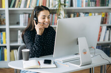 Caucasian Cheerful Young Woman, Call Center Worker, Teacher Or Manager, Wearing  A Headset, Looks At The Monitor While Discussing With Colleagues Or Clients Working Strategy