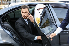 Businessman Getting Out Of Luxury Car