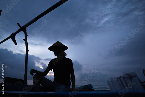 Portrait of a young male fisherman sitting on a boat with silhouette scenery