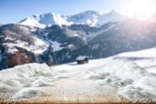 Fresh Snow On A Wooden Table Surrounded By An Alpine View Of The Mountains
