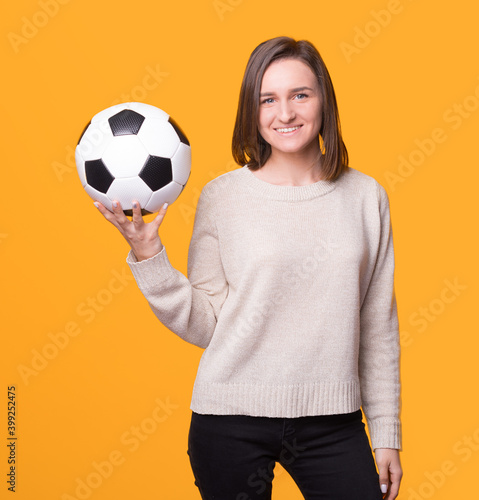 Foto Young woman is holding a soccer football ball over yellow background