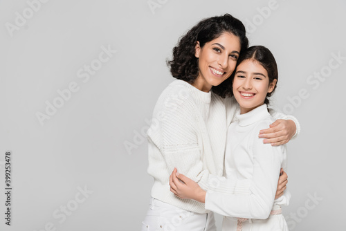 Obraz Curly hispanic woman hugging daughter isolated on grey, two generations of women - fototapety do salonu