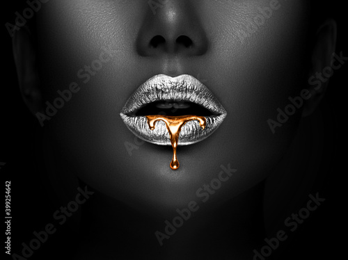 Fototapeta Golden lipstick closeup. Liquid metal dripping from silver lips. Beautiful makeup. Sexy lips, bright liquid paint on beauty African American model girl's mouth, close-up. Lipstick. obraz
