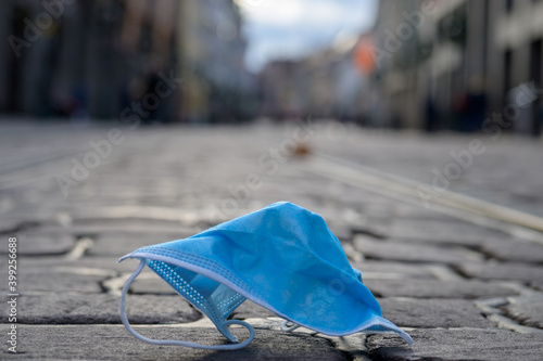 Used protective face mask discarded in a street - fototapety na wymiar