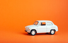 White Car On Colored Background. Model White Retro Toy Car On Orange Background. Miniature Car With Copyspace