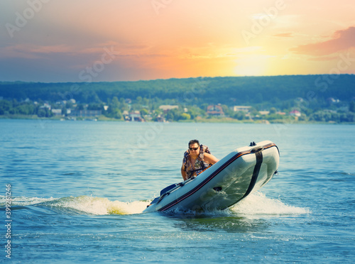 Canvas Print Man drives an inflatable motor boat in lake or sea