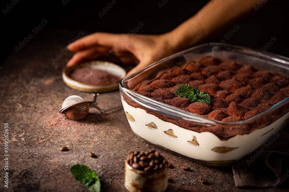 Fototapeta Traditional Italian dessert tiramisu in a glass backing form on dark background