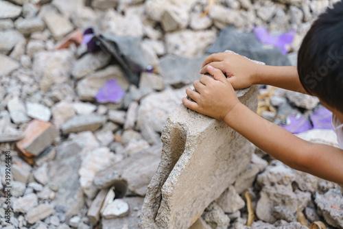 Fototapeta Kid hands finding something in concrete debris