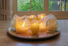 Melted Wax Candles On Plate On Dining Table.
