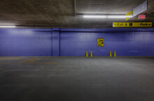 Underground Parking Lot With Traffic Cones And Blue Wall.