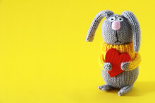 Sad, Cute, Knitted Hare In A Yellow Jacket With A Red, Wooden Heart In His Hands On Valentine's Day. Easter Gray Rabbit With Huge Ears On A Yellow Background. Copy Space.