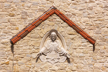 Sculpture Of Jesus Set Into Stone Wall.