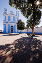 Church In A Town Square And A Shady Bench Under A Tree