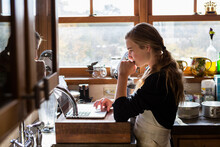 Teenage Girl In A Kitchen Following A Baking Recipe On A Laptop.