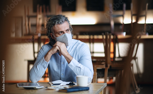 Obraz Frustrated owner sitting at table in closed cafe, small business lockdown due to coronavirus. - fototapety do salonu