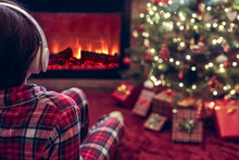 Alone Sad Woman In Headphones Sitting And Warming At Winter Evening Near Fireplace Flame And  Christmas Tree.