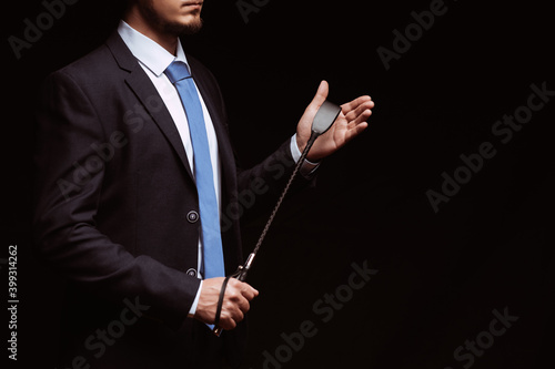 Fotografie, Obraz Male dominant businessman in a suit holding a leather whip Flogger for dominatio