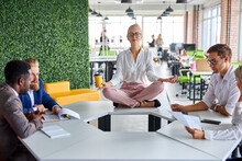 Young Caucasian Woman Meditating In Office While Colleagues Are Working, Keep Calm, Meditate. Sits On Table With Crossed Legs