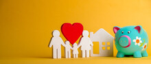 Piggy Bank With Figures Of Family And House And Red Heart. Piggybank Isolated On Yellow Background. Investing In Future.