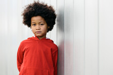 Black Child With Afro Hair, Looking At The Camera With A Serious Expression, In A Wall Of The Street Background. Kids And Black People Concept