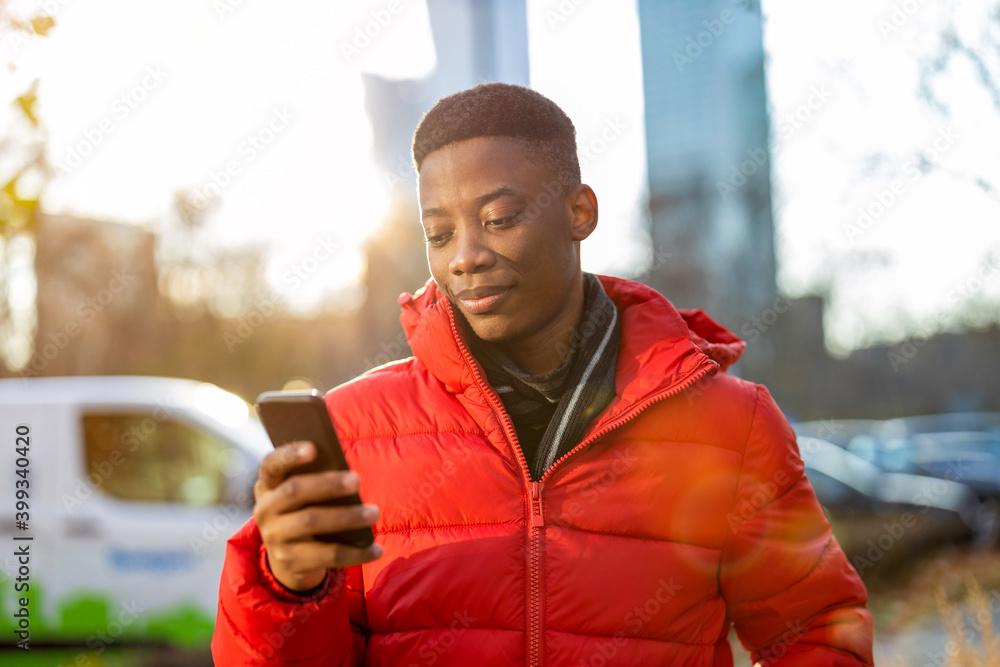 Obraz Young man using smart phone outdoors at urban setting  fototapeta, plakat