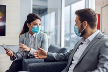Friendly Car Seller With Face Mask Sitting With Customer In Car Salon, Holding Tablet And Talking About Specifications And Performances Of Car During Corona Virus.