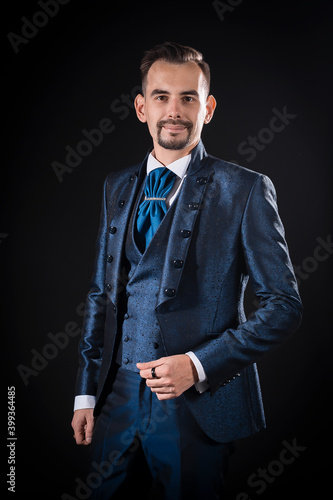 Canvas Print Handsome man with mustache and beard in blue tuxedo smiling on black background