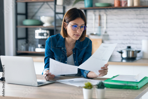 Pretty young business woman working with computer while consulting some invoices and documents in the kitchen at home. - fototapety na wymiar