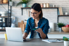 Cute Young Woman Holding White Credit Card For Shopping Online With Computer While Sitting In The Kitchen At Home.