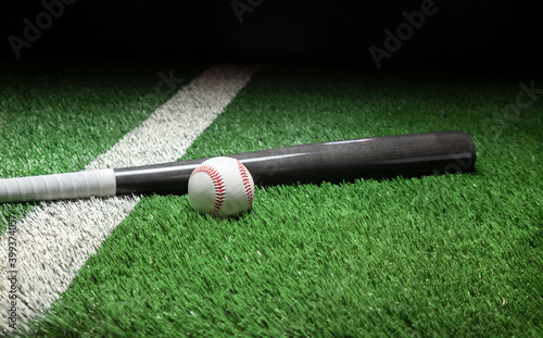 Fotografie, Tablou Baseball and gray bat on field with stripe and dark background