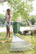 Girl Raking Leaves In Garden