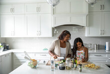 Mother And Daughter Preparing Meal In Kitchen
