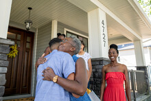 Family Welcoming And Hugging Woman At Front Porch