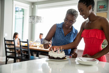 Mother And Daughter Lighting Candles On Cake