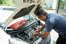 Man Fixing Car With Hood Up