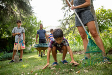 Boy Doing Gardening Chores With Family