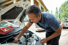 Man Fixing Car In Porch