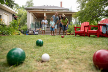 Family Playing Lawn Bowl In Backyard