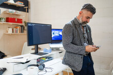 Startup Business Owner Texting On Phone At Desk