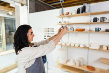Owner Of Ceramics Startup Photographing Pottery Display