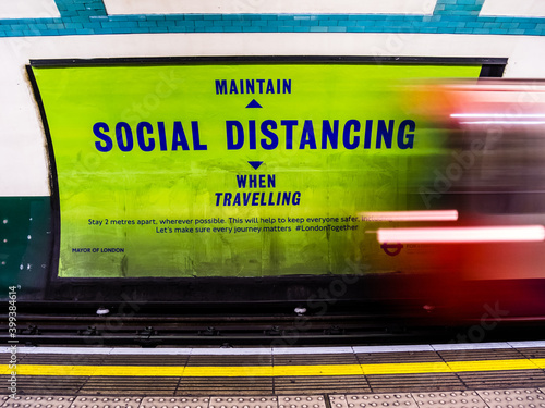 """London UK,December 12th 2020: Russell Square London underground tube station. A large platform poster to remind commuters to """"Maintain social distancing"""" when travelling. During Covid-19, Coronavirus"""