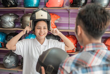 Young Women Choose A Helmet And Wear It When Served By A Shop Assistant In A Helmet Shop